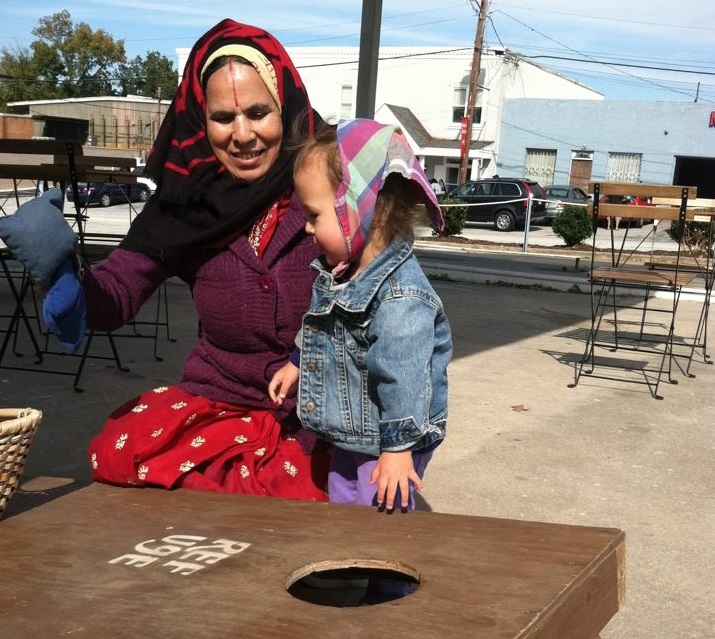 Sage rocks the head scarf as she learns bean bag toss at Refuge Coffee